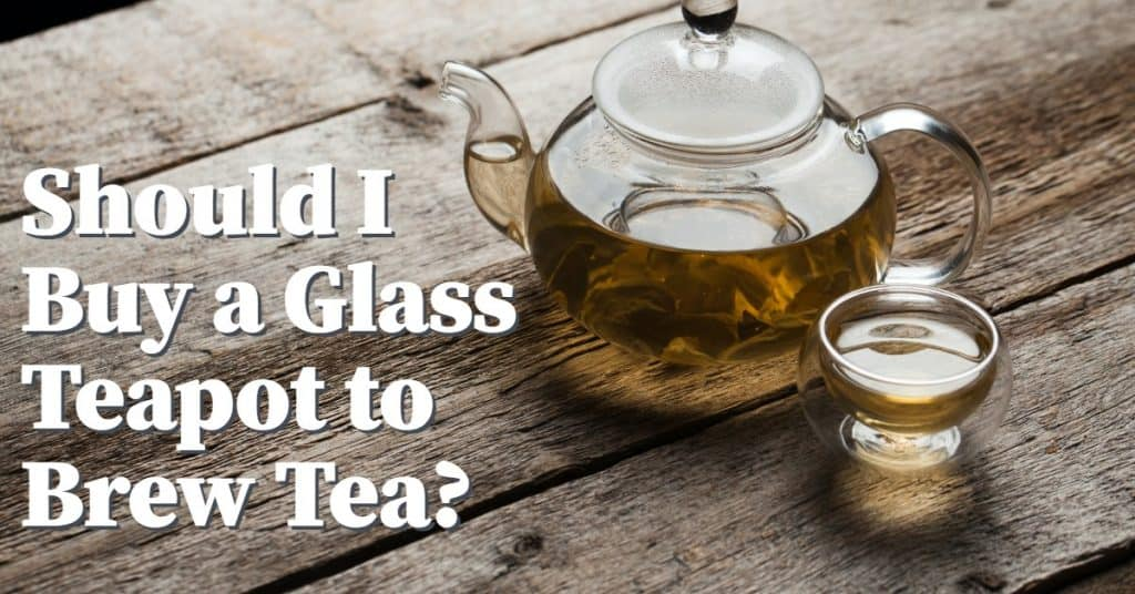 glass teapot with tea inside and cup beside it