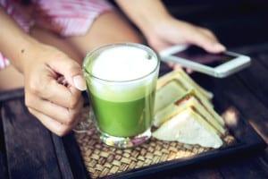 Woman holding matcha green tea latte