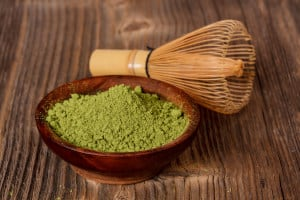 Matcha green tea powder in a bowl on a table next to a whisk