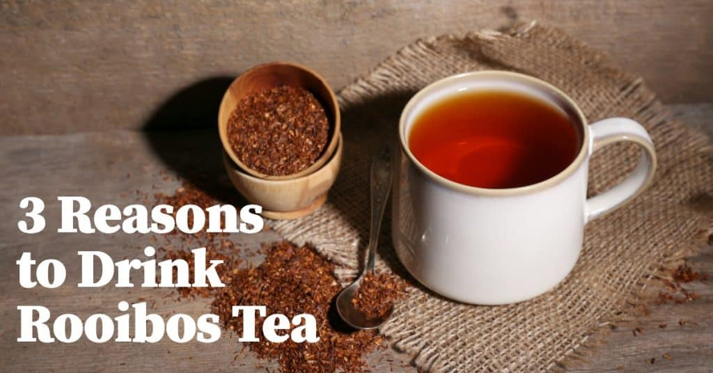 rooibos tea next to spoon and cup and leaves